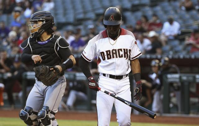 Arizona Diamondbacks' Jarrod Dyson, right, walks back to the dugout after striking out as Colorado Rockies catcher Tony Wolters throws the ball to the third baseman during the first inning of a baseball game Wednesday, June 19, 2019, in Phoenix. (AP Photo/Ross D. Franklin)