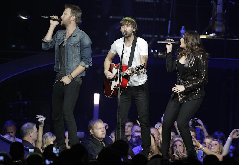 "Lady Antebellum's Charles Kelly, Dave Haywood and Hillary Scott perform Wednesday, May 16, 2012, in Louisville, Ky. The Grammy-winning Lady Antebellum trio will staged a ""mini-prom"" bash for students from Henryville Junior-Senior High School, followed by a benefit for the devastated community. (AP Photo/Darron Cummings)"