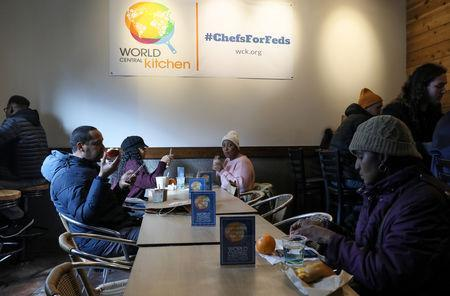 Federal workers left unpaid or furloughed by the extended partial government shutdown eat free food and drink coffee at the World Central Kitchen, a volunteer emergency kitchen run by Chef Jose Andres, in Washington, U.S. January 16, 2019. REUTERS/Jonathan Ernst