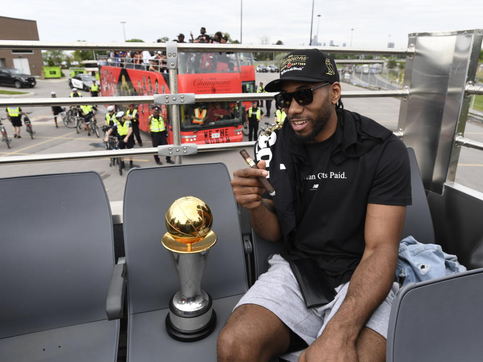 Toronto Raptors forward Kawhi Leonard smokes a cigar as he sits with his playoffs MVP trophy during the 2019 Toronto Raptors NBA basketball championship parade in Toronto, Monday, June 17, 2019. (Frank Gunn/The Canadian Press via AP)