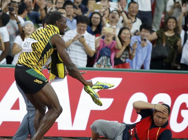 Winner Bolt of Jamaica gets up after being hit by a cameraman on a Segway (R) after competing at the men's 200 metres final during the 15th IAAF World Championships at the National Stadium in Beijing