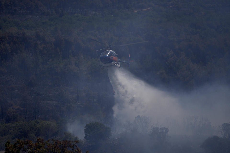 An helicopter drops water on a wildfire near Le Luc, southern France, Thursday, Aug. 19, 2021. A fire that has ravaged forests near the French Riviera for four days is slowing down as winds and hot weather subside, but more than 1,100 firefighters were still struggling to get it under control Thursday, local authorities said. (AP Photo/Daniel Cole)