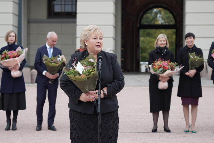 Norway's Prime Minister Erna Solberg with her outgoing government speaks outside the Royal Palace in Oslo, Thursday Oct. 14, 2021. Norway's Conservative Prime Minister Erna Solberg will step down as head of a three-party, minority center-right government after the left-leaning bloc won last month's parliament election. (Ole Berg-Rusten/NTB via AP)