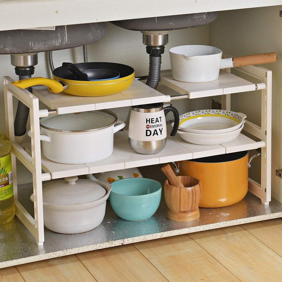 <p>This <span>OBOR Expandable Under Sink Organizer</span> ($33) makes it possible to store pots and pans in that awkward space.</p>
