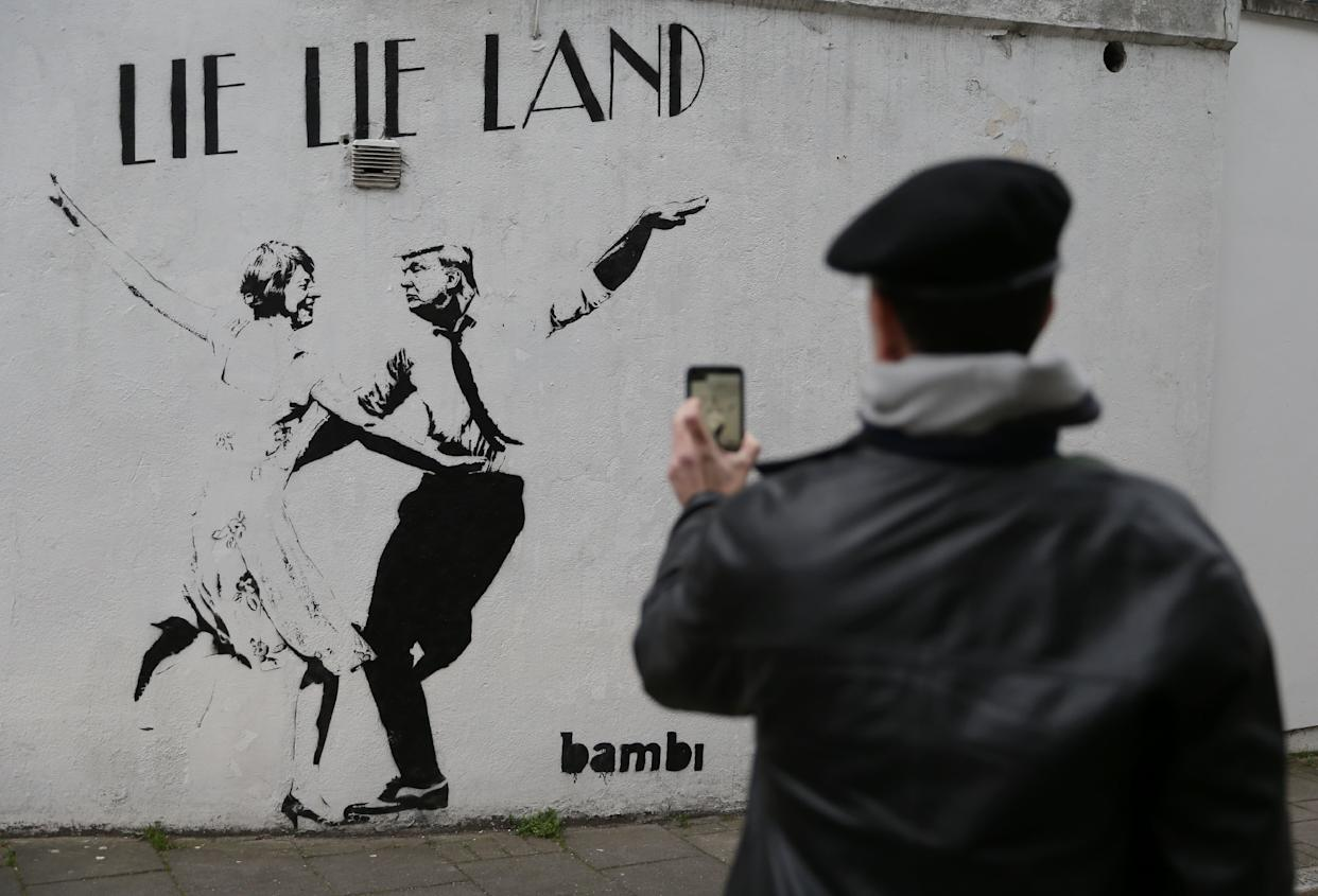 A man takes a picture of a mural by English street artist Bambi depicting British Prime Minister Theresa May dancing with US President Donald Trump in London on February 22, 2017.