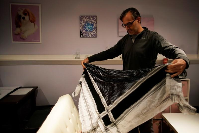 Mark Giaconia, who served for 20 years in the U.S. Army, of which 15 years in the U.S. Special Forces and was embedded with the Kurds in Iraq, folds his Kurdish scarf at his house in Herndon