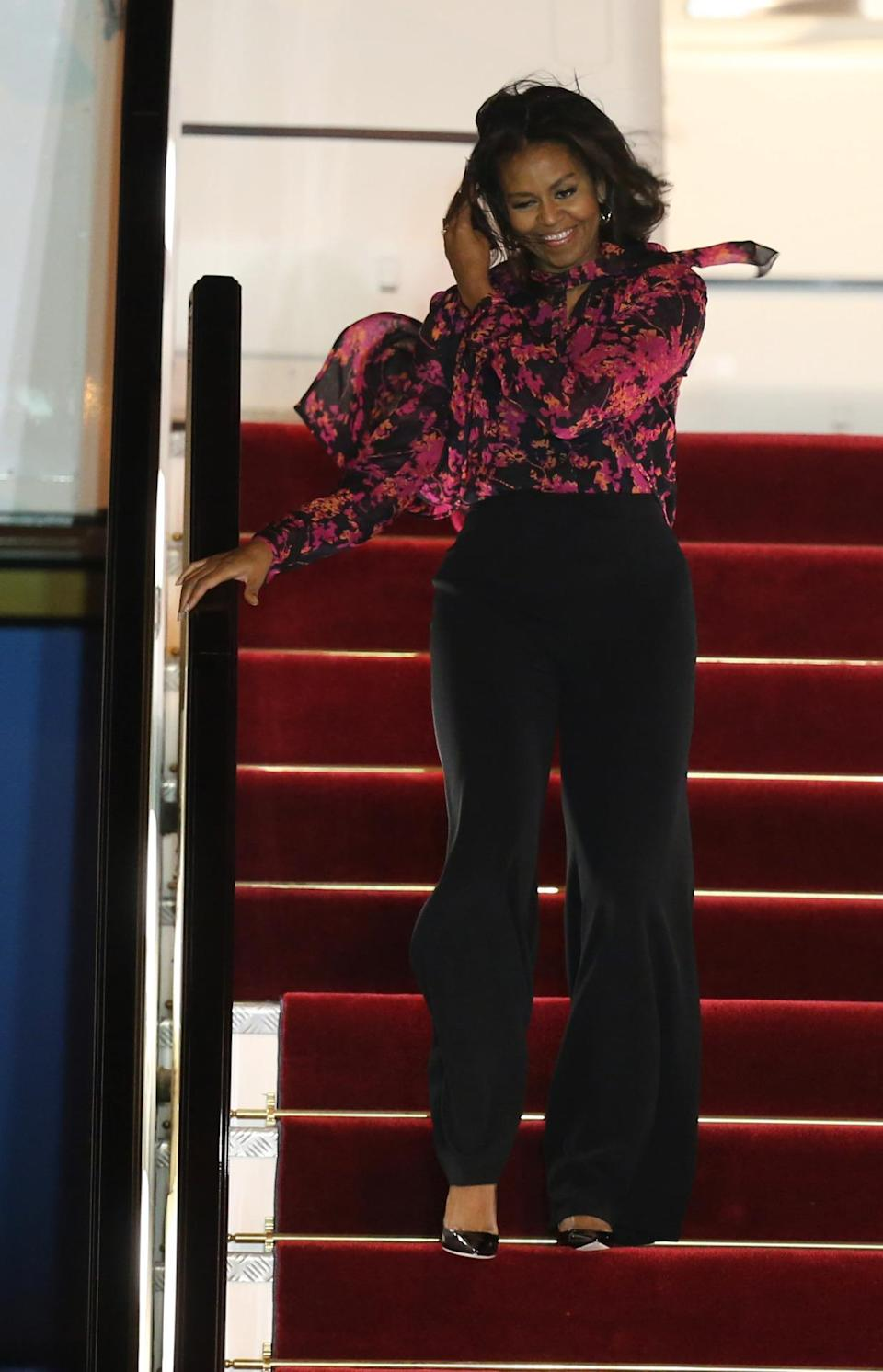 <p>The first lady showed that flying outfits can be both chic and comfortable in a floral blouse and black high-waisted flares. You better believe she kicked her patent heels off on Air Force One during the long journey. <i>Photo: AP</i></p>