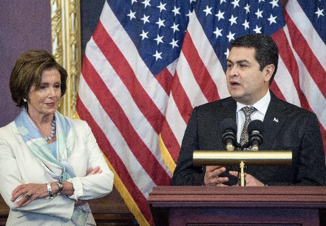 Honduran President Juan Orlando Hernandez (R) delivers remarks as US House of Representatives Democratic Leader Nancy Pelosi listens, on July 24, 2014 in Washington
