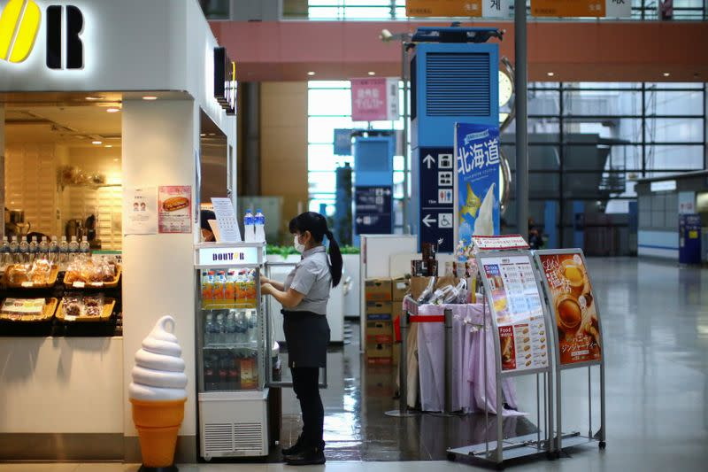 A vendor, wearing protective mask following an outbreak of the coronavirus disease (COVID-19), works at the almost empty Kansai International Airport in Osaka