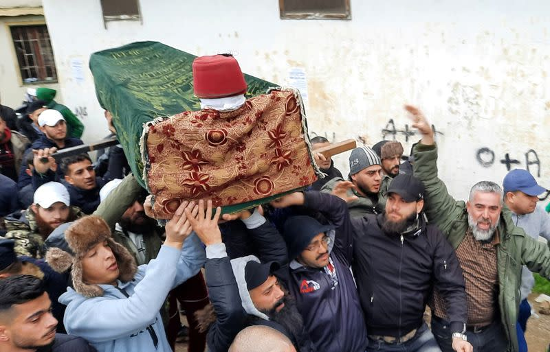 People carry the coffin of a protestor during his funeral in Tripoli