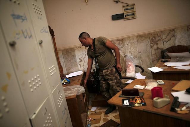<p>A member of the Iraqi Army's 9th Armoured Division searches through a desk inside a compound used as a prison by Islamic State militants in the 17 Tamuz (July 17) district, in western Mosul, Iraq, June 6, 2017. (Alkis Konstantinidis/Reuters) </p>