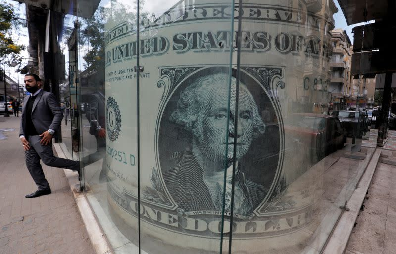 FILE PHOTO: Man leaves a currency exchange bureau showing an image of the U.S. dollar in Cairo