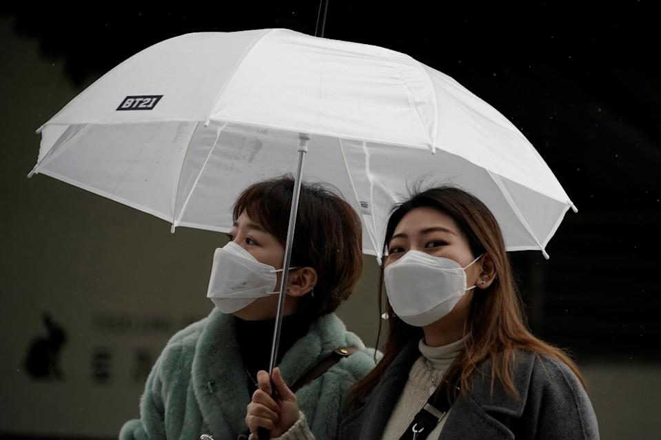 Passengers wearing masks to prevent contacting the coronavirus walk outside Seoul Railway Station in Seoul, South Korea, February 25, 2020.   REUTERS/Kim Hong-Ji