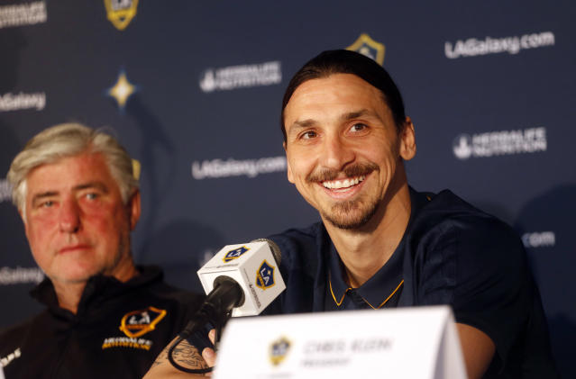 LA Galaxy's newest player Zlatan Ibrahimovic, right, of Sweden, smiles during an MLS soccer press conference at the StubHub Center, March 30, 2018 in Carson, Calif. Listening at left is Galaxy coach Sigi Schmid. (AP Photo/Ringo H.W. Chiu)