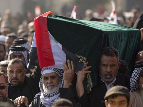 Iraqis carry a mock coffin as they march in a symbolic funeral procession (AFP)