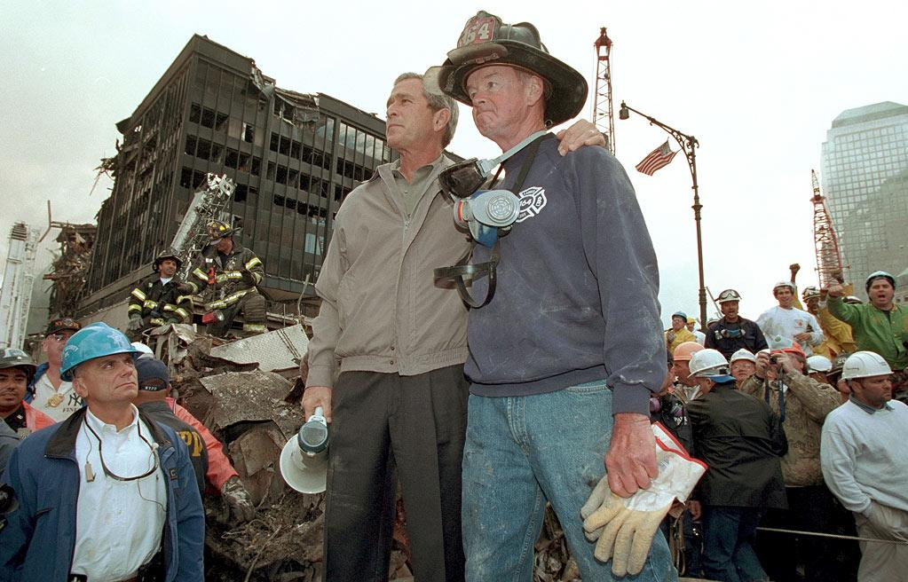 """The President visits the site of the World Trade Center disaster.  He greets firefighters, police, and rescue personnel.  The President uses a bullhorn to address the rescue workers.  He puts his arm around retired fireman Bob Beckwith from ladder 117  as seen on """"George W. Bush:  The 9/11 Interview."""""""
