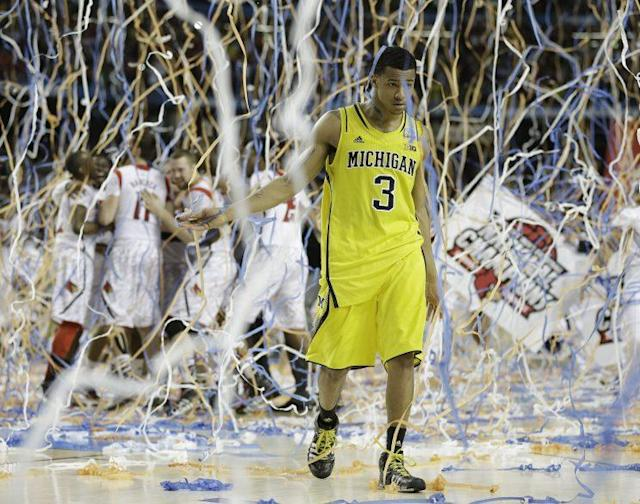 Michigan's Trey Burke (3) walks off the court as Louisville celebrate its win during the NCAA college basketball championship game on April 8, 2013, in Atlanta. (AP)