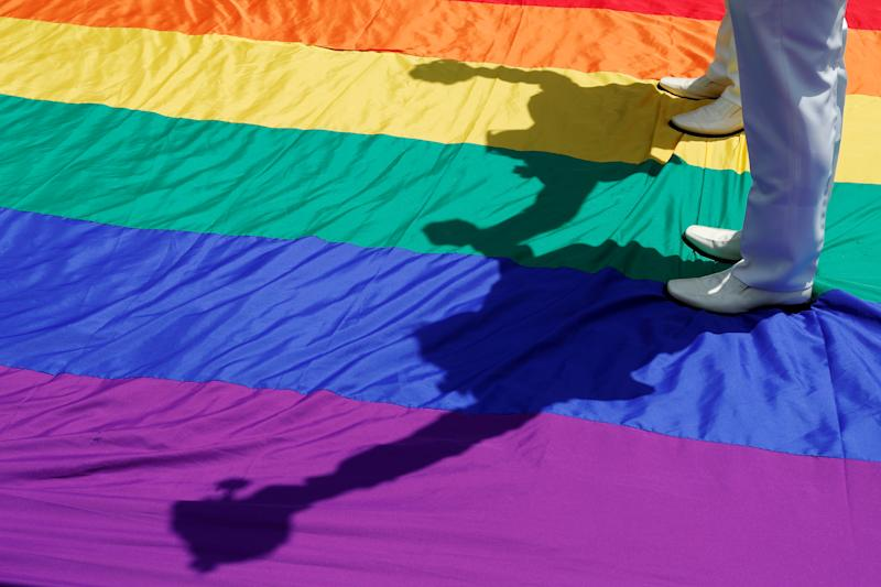 Gay newlyweds walk on a giant rainbow flag at a pro same-sex marriage party after registering their marriage in Taipei, Taiwan May 24, 2019. REUTERS/Tyrone Siu TPX IMAGES OF THE DAY