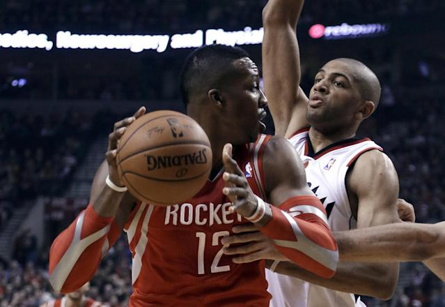 Houston Rockets center Dwight Howard, left, looks for an opening against Portland Trail Blazers forward Nicolas Batum during the first half of Game 3 of an NBA basketball first-round playoff series in Portland, Ore., Friday, April 25, 2014. (AP Photo/Don Ryan)
