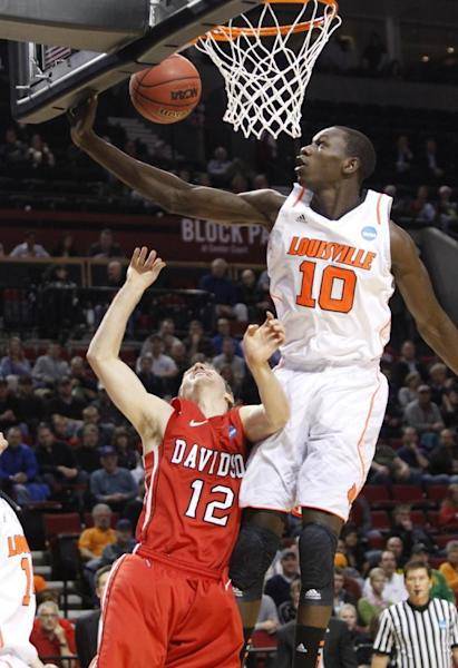 Louisville center Gorgui Dieng, right, blocks a shot by Davidson guard Nik Cochran during the first half of their NCAA tournament second-round college basketball game in Portland, Ore., Thursday, March 15, 2012.(AP Photo/Don Ryan)