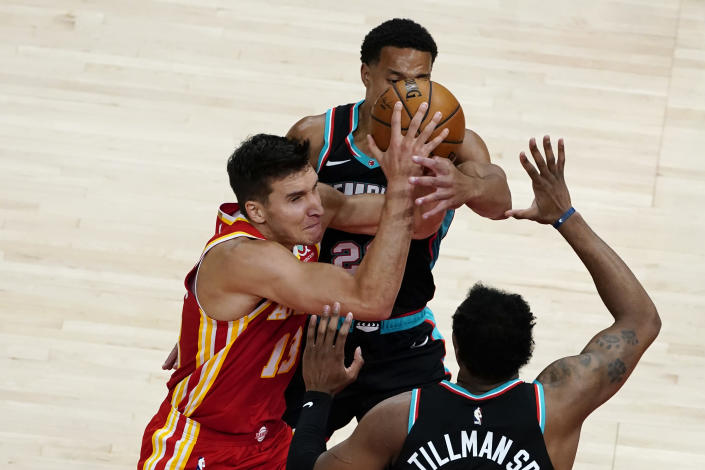 Atlanta Hawks guard Bogdan Bogdanovic (13) is defended by Memphis Grizzlies guard Desmond Bane (22) as he tries to shoot in the first half of an NBA basketball game Wednesday, April 7, 2021, in Atlanta. (AP Photo/John Bazemore)
