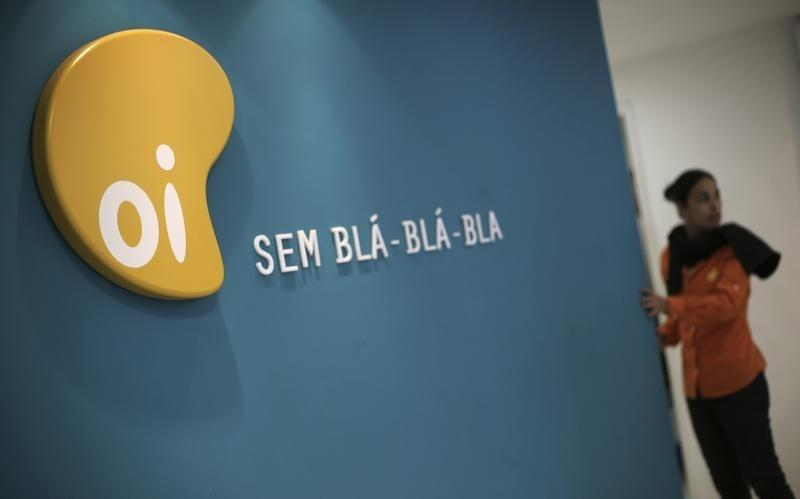 A woman stands next to the logo of Brazil's largest fixed-line telecoms group Oi, inside a shop in Sao Paulo