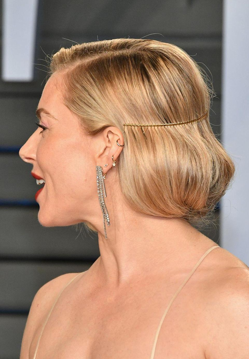 <p>To offset her 1920s-styled hair, Sienna matches diamond drop earrings with a helix gold hoop with a stylish array of modern, dainty spiritual symbols. Beaut! </p>