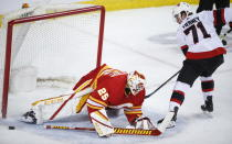 Ottawa Senators' Chris Tierney, right, shoots wide of the net as Calgary Flames goalie Jacob Markstrom covers the post during the second period of an NHL hockey game, in Calgary, Alberta, Sunday, March 7, 2021. (Jeff McIntosh/The Canadian Press via AP)