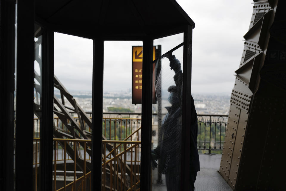 French employee cleans the window during the opening up of the top floor of the Eiffel Tower, in Paris, Wednesday, July 15, 2020. The top floor of Paris' Eiffel Tower reopened today as the 19th century iron monument re-opened its first two floors on June 26 following its longest closure since World War II. (AP Photo/Francois Mori)