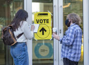 An Elections Canada worker, right, holds a voter's coffee as they record COVID-19 contact-tracking information at the Halifax Convention Centre as they prepare to vote in the federal election in Halifax on Monday, Sept. 20, 2021. (Andrew Vaughan/The Canadian Press via AP)