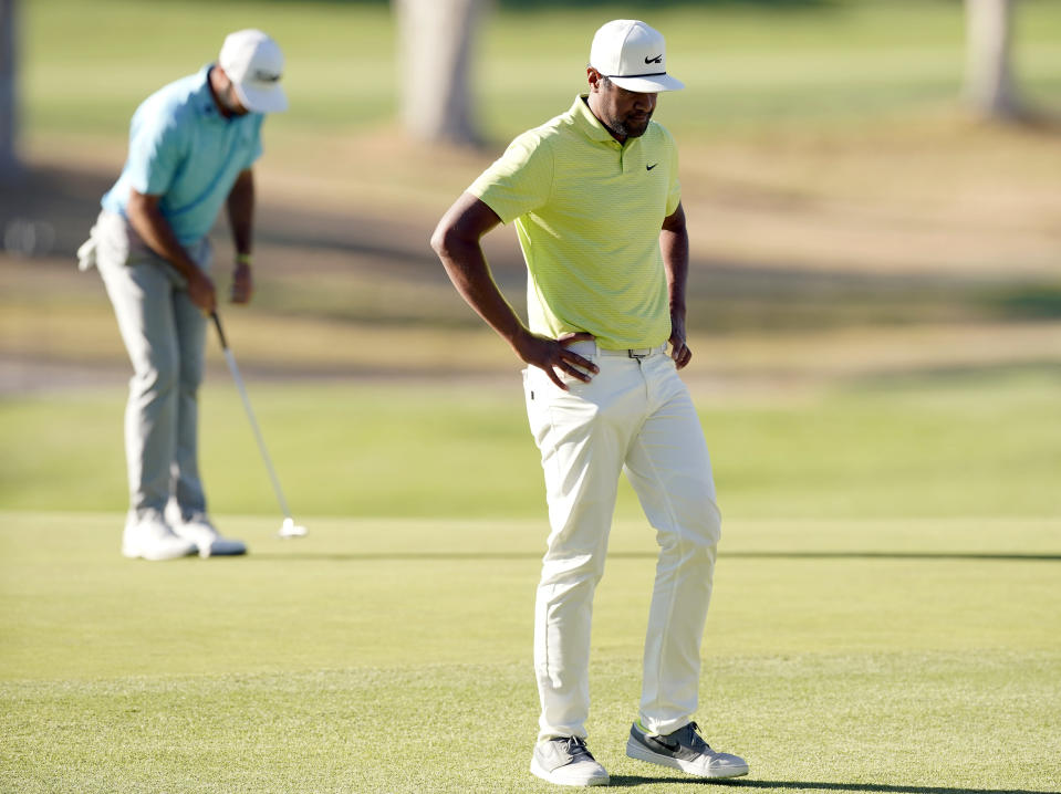 Tony Finau, right, reacts after missing a putt on the 10th green as Max Homa putts, back left, during the first playoff hole in the final round of the Genesis Invitational golf tournament at Riviera Country Club, Sunday, Feb. 21, 2021, in the Pacific Palisades area of Los Angeles. (AP Photo/Ryan Kang)
