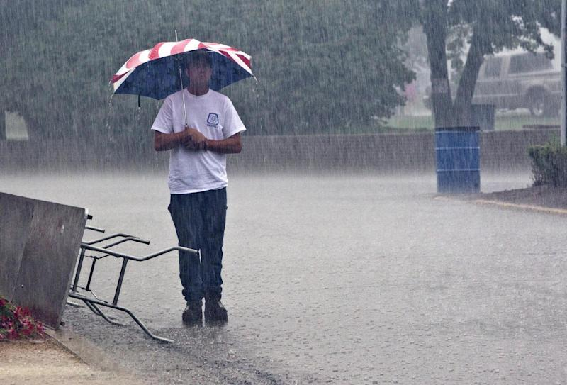 David Walker endures the rain from the remnant of Hurricane Isaac during opening ceremonies of the 29th Annual Labor's Family Day Picnic Saturday, September 1, 2012, at Columbian Park in Lafayette, Ind. (AP Photo/Journal & Courier, Michael Heinz) MANDATORY CREDIT; NO SALES