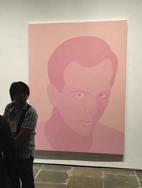 "A patron stands next to ""Peach Oswald"" (2001) by Wayne Gonzales"