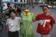 Idania Del Río, left, and Leire Fernández, owners of Clandestina, pose with a mannequin dressed in clothes they created, outside their store in Havana, Cuba, Feb. 18, 2021. Tourists poured through their shop until the Trump administration turned off the taps that had been opened just a few years before by then-President Barack Obama. Today, the doors swing open less often, with tourism choked both by U.S. sanctions meant to punish Cuba's government and a pandemic that has squashed tourism almost everywhere. (AP Photo/Ramon Espinosa)