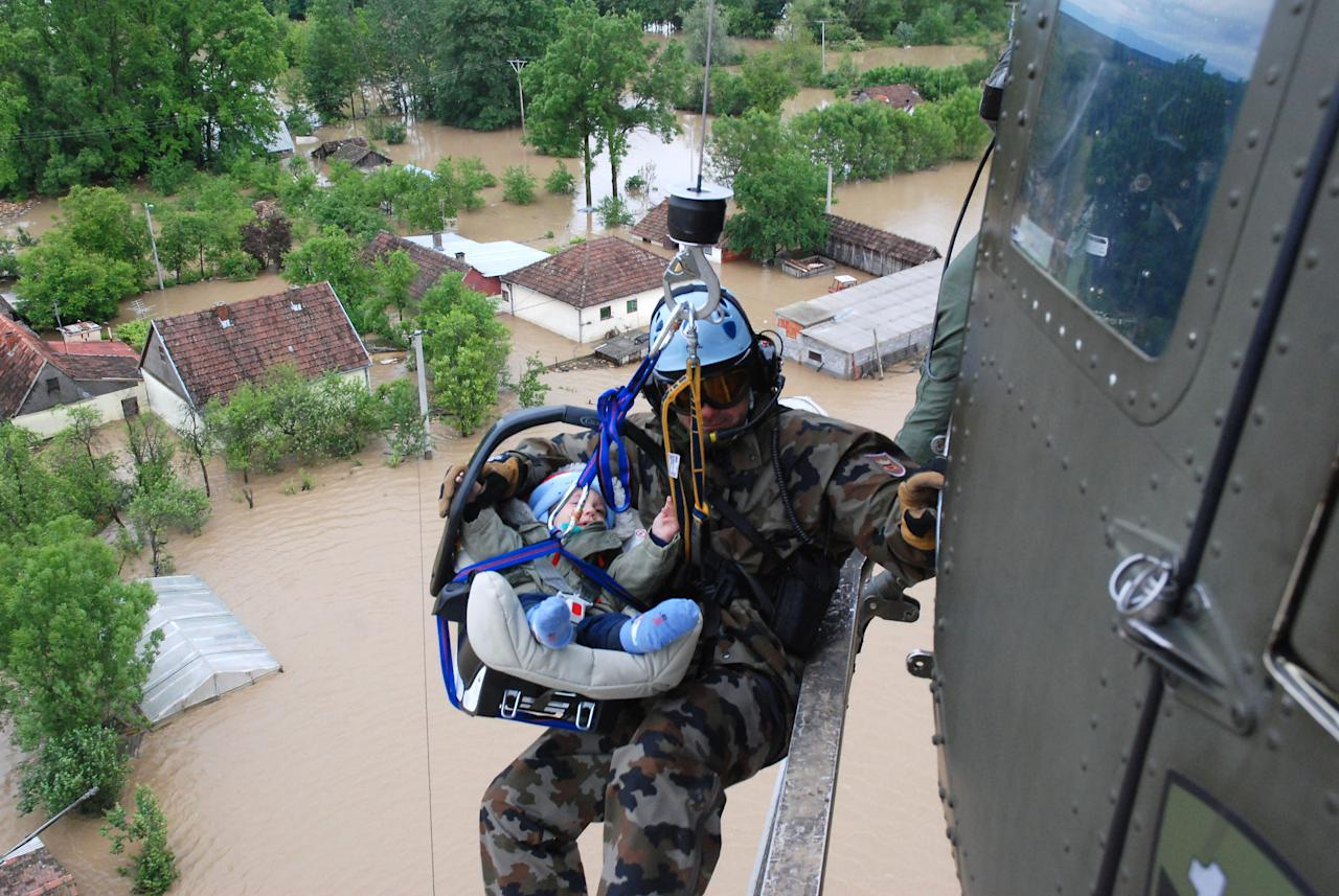 In this picture taken on Saturday, May 17, 2014, and made available Tuesday May 20, 2014 a Slovenian army helicopter team rescues a small baby by winching the baby carrier into the helicopter over the village of Tisina, near Bosanski Samac, northern Bosnia-Herzegovina. The rest of the baby's family was evacuated later on, the rescue team said. Hundreds of thousands of people were forced from their homes in Bosnia and Serbia following the worst flooding since record began 120 years ago. (AP Photo/1.st lt. Rok Einhauer, 151.Helicopter squadron, Slovenian Army)