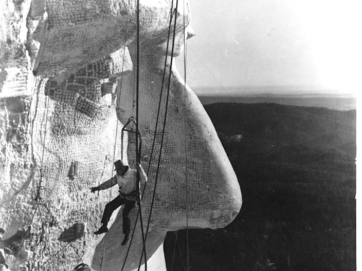 The face of Abraham Lincoln under construction on Mount Rushmore in 1936 with Gutzon Borglum monitoring the work.