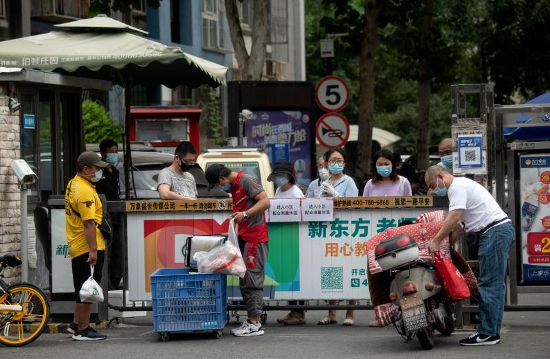 People wearing face masks wait for the delivery of goods they ordered online in a residential area in Xicheng district which is under lockdown after a new COVID-19 coronavirus outbreak near the closed Xinfadi Market in Beijing on June 17, 2020. - Beijing's airports cancelled two-thirds of all flights and schools in the Chinese capital were closed again on June 17 as authorities rushed to contain a new coronavirus outbreak linked to the Xinfadi wholesale food market. (Photo by NOEL CELIS / AFP) (Photo by NOEL CELIS/AFP via Getty Images)