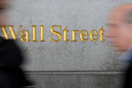 FILE PHOTO: People walk by a Wall Street sign close to the New York Stock Exchange (NYSE) in New York, U.S., April 2, 2018. REUTERS/Shannon Stapleton/File Photo