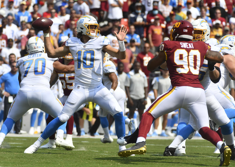 Sep 12, 2021; Landover, Maryland, USA; Los Angeles Chargers quarterback Justin Herbert (10) attempts a pass as Washington Football Team defensive end Montez Sweat (90) rushes during the first quarter at FedExField. Mandatory Credit: Brad Mills-USA TODAY Sports