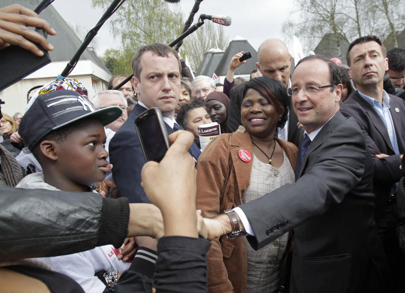 French Socialist Party candidate for the 2012 presidential elections Francois Hollande shakes hands with locals as he visits Les Ulisin, a southern suburb of Paris, Saturday, April 7, 2012. (AP Photo/Michel Euler)