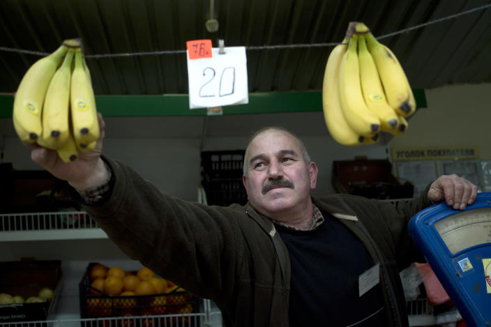 A street vendor hangs bananas on a rope with prices in rubles and hryvnias in Simferopol, Crimea, Wednesday, March 26, 2014. The Russian ruble earlier this week entered official circulation in Crimea, which voted in a contentious referendum earlier this month to break away from Ukraine and join Russia. (AP Photo/Pavel Golovkin)