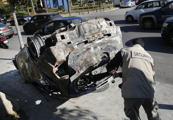 A private security worker takes pictures of a burned car that was set on fire early Tuesday by supporters of the Shiite Hezbollah and Amal Movement groups, in Beirut, Lebanon, Tuesday, Dec. 17, 2019. Supporters of Lebanon's two main Shiite groups Hezbollah and Amal clashed with security forces and set fires to cars in the capital early Tuesday, apparently angered by a video circulating online that showed a man insulting Shiite figures.(AP Photo/Hussein Malla)