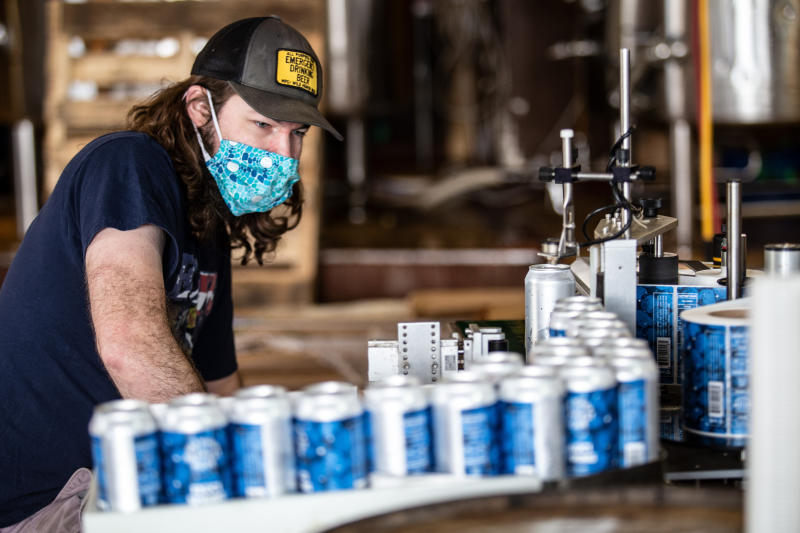 """Colin Conroy operates a labeling machine as cans of """"Fauci Spring"""" beer are labeled at Wild Heaven Beer on Thursday, April 30, 2020, in Avondale Estates, Ga. The pale ale was named to honor Dr. Anthony Fauci, the director of the National Institute of Allergy and Infectious Diseases and President Donald Trump's point person on explaining the COVID-19 pandemic to the American public. (AP Photo/Ron Harris) /// Here are the final 2 photos. Thank you. Ron Harris Social Media Editor/Reporter 101 Marietta St. NW, Suite 2450 Atlanta, Ga. 30303 (404) 653-8460 office (503) 329-1861 Twitter: @Journorati"""