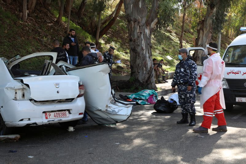 Members of the Lebanese police stand next to a damaged car in Hadath