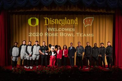Football players and coaches with the Oregon Ducks and Wisconsin Badgers pose with Mickey Mouse, Tournament of Roses President Laura Farber (center left), Vice President of Disneyland Park Kris Theiler (center right) and Disneyland Ambassador Rafa Barron, during the teams' visit to Disneyland Park on Dec. 26, 2019, their first official stop on the way to the New Year's Day 106th Rose Bowl Game. (Joshua Sudock/Disneyland Resort)