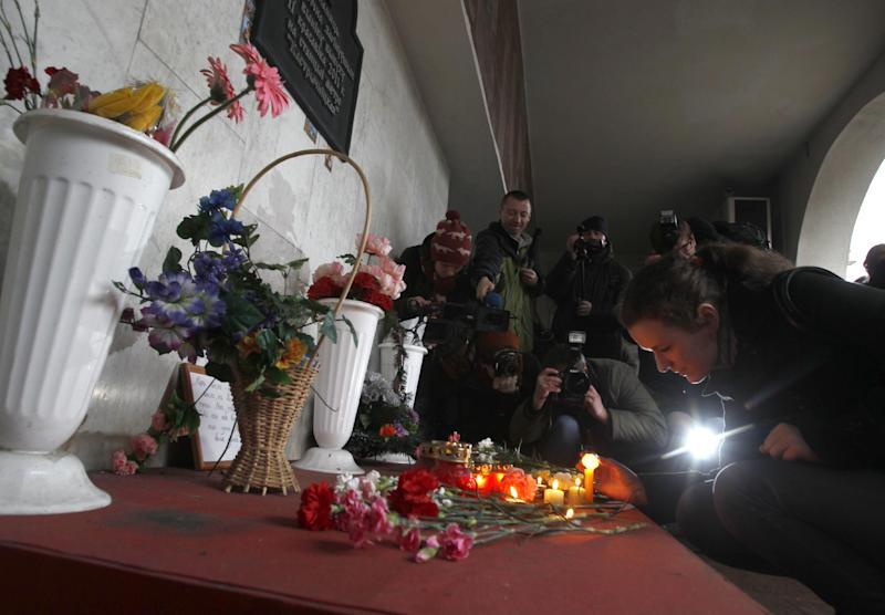 Belarusian lays flowers to memorial board to victims of last year subway blast  in Minsk, Belarus, Friday, March 16, 2012.  Belarus' president has denied clemency to two men sentenced to death for last year's bombing in the capital's subway that killed 15 people. State television reported Wednesday that President Alexander Lukashenko rejected the clemency appeal. The men could be executed anytime. (AP Photo/Sergei Grits)