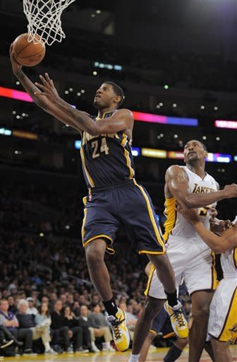 Indiana Pacers guard Paul George puts up a shot as Los Angeles Lakers forward Metta World Peace defends during the first half of their NBA basketball game, Sunday, Jan. 22, 2012, in Los Angeles, Calif. (AP Photo/Mark J. Terrill)