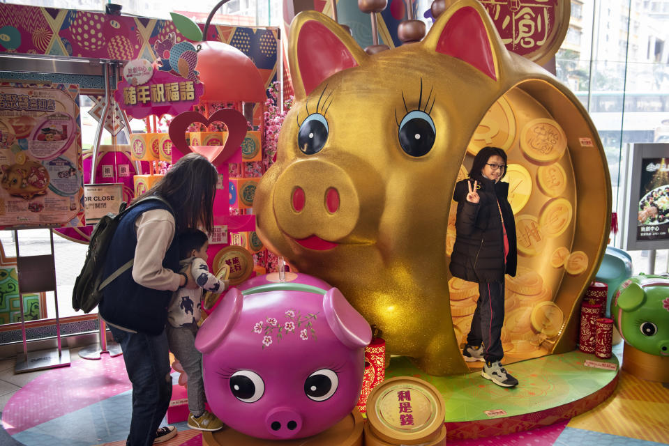 Locals and tourists in Hong Kong seen taking pictures next to a large decorative pig commemoration during the preparation for the Lunar Chinese New Year 2019. Image: Getty