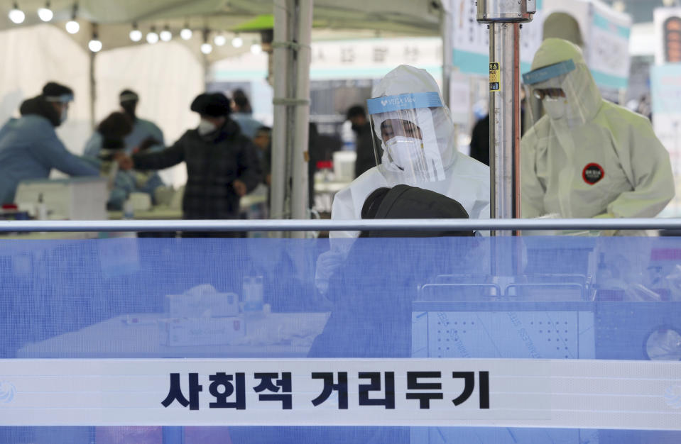 "A medical worker wearing protective gear takes sample during a COVID-19 testing at coronavirus testing site in Seoul, South Korea, Saturday, Dec. 26, 2020. The letters read "" Social Distancing."" (Hong Hyosik/Newsis via AP)"