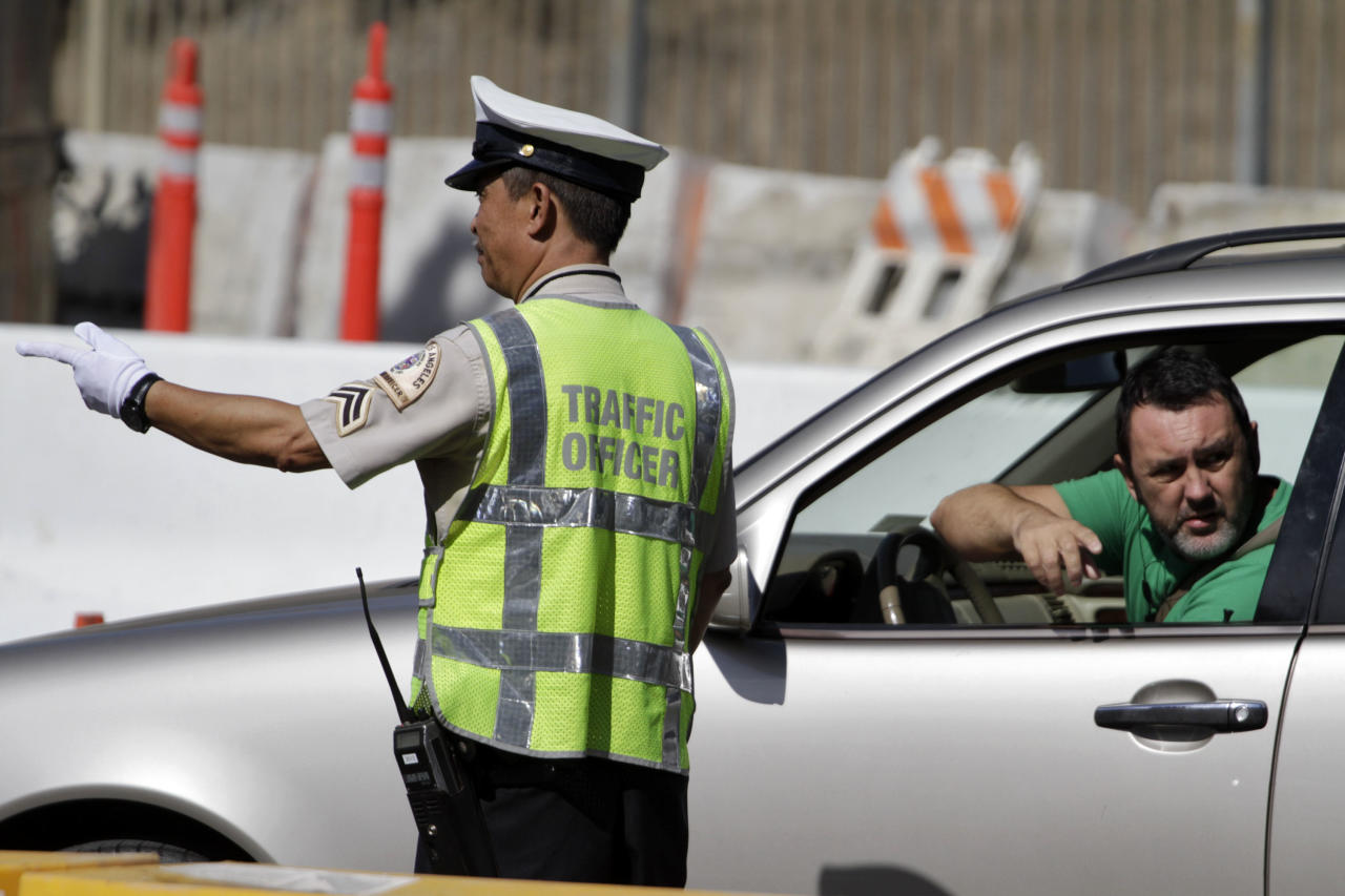 A Los Angeles traffic officer assists a driver at the road closure where construction crews are demolishing a portion of the Mulholland Drive bridge that spans the 405 Freeway September 29, 2012 in Los Angeles, California. The 405 Freeway was completely shut down for a 10 mile stretch this weekend for the demolition that is part of a larger $1-billion freeway improvement project. (Photo by Jonathan Alcorn/Getty Images)